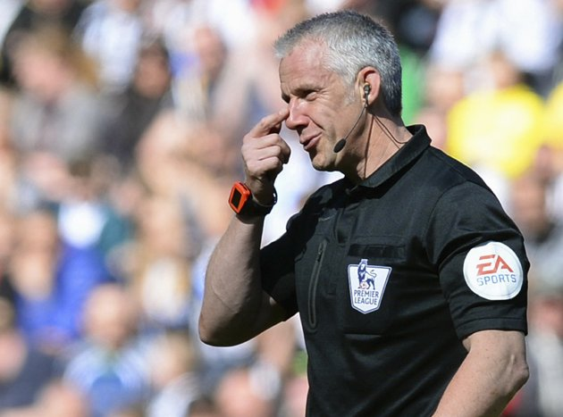 Referee Foy reacts after being hit in the face by a football during the English Premier League soccer match between Newcastle United and Swansea City at St James' Park in Newcastle