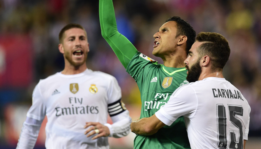 Real Madrid's Costa Rican goalkeeper Keylor Navas (2ndR) reacts after stopping a penalty kick past Real Madrid's defender Dani Carvajal (R) during the Spanish league football match Club Atletico de Madrid vs Real Madrid CF at the Vicente Calderon stadium in Madrid on October 4, 2015.   AFP PHOTO/ JAVIER SORIANO